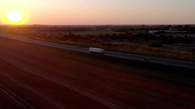 Large Delivery Truck is Moving Setting Sun. Aerial Shot Of Truck On Road In Beautiful Countryside in Sunset. Aerial View of Semi-truck on Road With Sunset In Background.