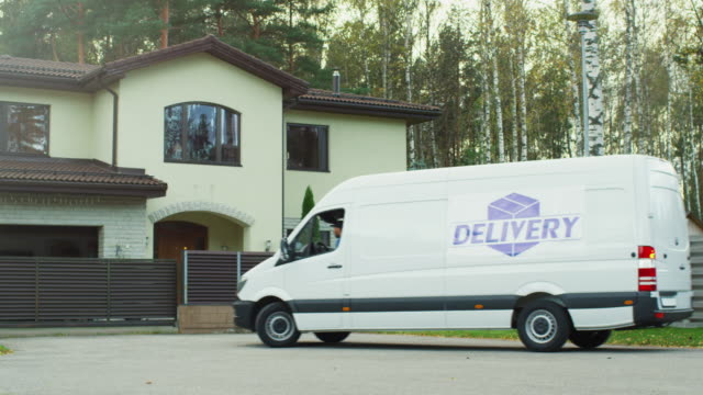 Large Delivery Van Drive to Suburban House and Delivery Man Comes Out. Sunny Autumn with Yellow Birches and Pines is on the Background. video