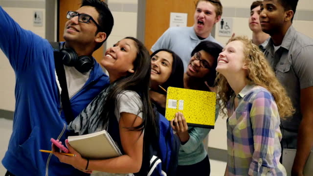 Large diverse group of high school students smiling and posing for selfie photo video