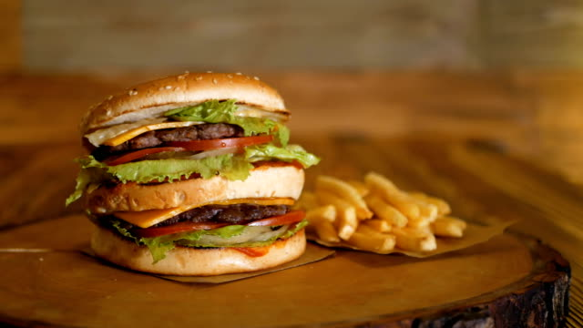 A large double burger is lying on a wooden board next to French fries. Professionally cooked fast food.