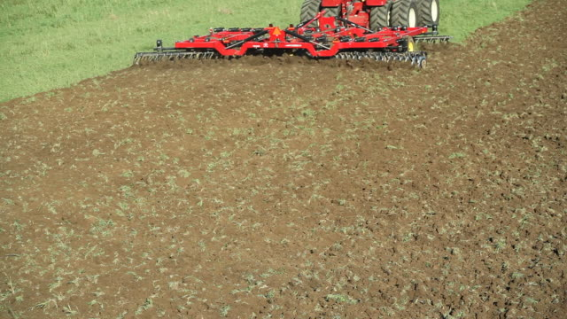 Large Eight Tire Tractor Plowing Farm Field