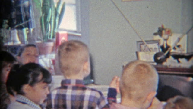 1965: Large family of youngsters sitting around the golden television. . electrical equipment stock videos & royalty-free footage