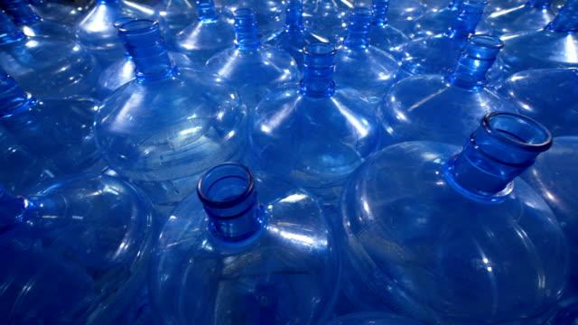 A large field of empty open 5 gallon bottles. video