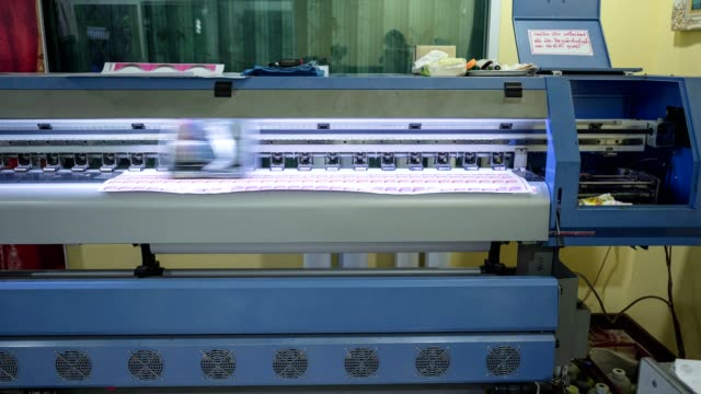 Large format inkjet printer working on sticker sheet with branding and technician