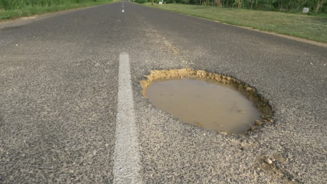 LOW ANGLE: Large gaping pothole filled with muddy water sticks out of empty road video