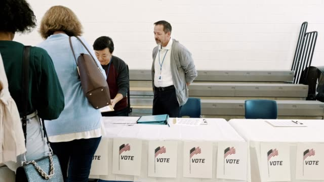 Large group of diverse voters wait in long line to receive ballot