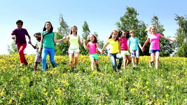 Large group of kids run in dandelion field video