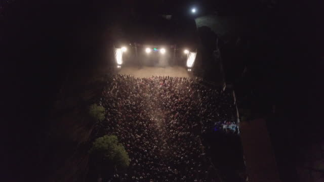 Large group of people at concert 4k Aerial view of a ;arge group of people, having fun on music  festival, at the city at night. 4k resolution large stock videos & royalty-free footage