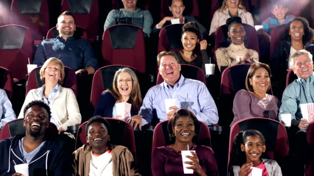 Large group of people in movie theater watching comedy A large group of people of mixed ages, including men, women, boys and girls, watching a funny movie in a movie theater. audience stock videos & royalty-free footage