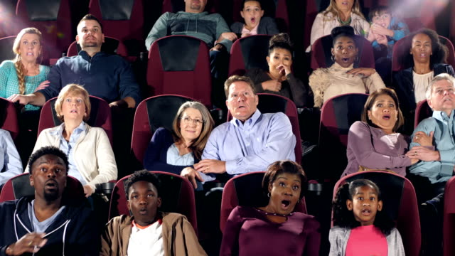 Large group of people in theater watching scary movie