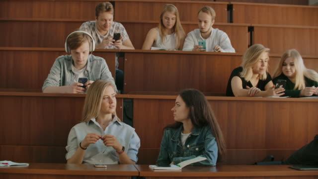 eine große gruppe von schülern in der pause kommuniziert miteinander im klassenzimmer. große klasse - vorlesungsfrei stock-videos und b-roll-filmmaterial