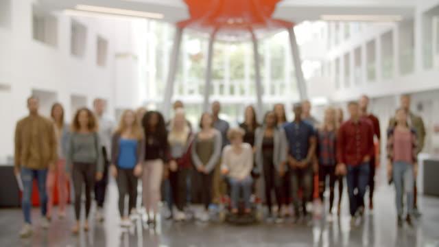 stor grupp studenter flyttar in i fokus i universitets lobby - multietnisk grupp bildbanksvideor och videomaterial från bakom kulisserna