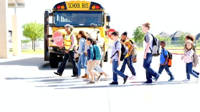 Large group of students walk across crosswalk in front of school building video