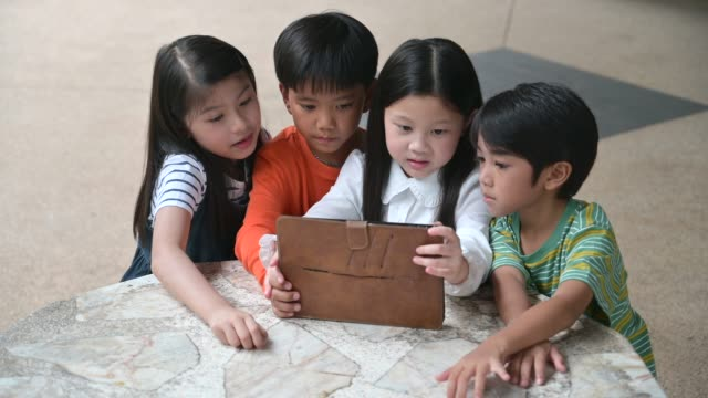 Large group of young boys and girls sharing a tablet and smart phone technology