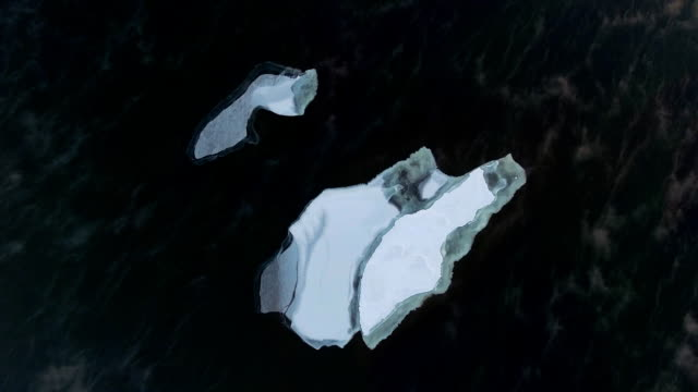Large ice floe sails in the midst of dark water, shot from above Large ice floe sails in the midst of dark water, shot from above. ice drifts in open water, a quadrocopter. icecap stock videos & royalty-free footage