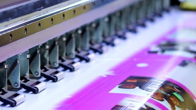 Large Inkjet printer working on vinyl banner Large Inkjet printer working pink color on vinyl banner printmaking technique stock videos & royalty-free footage