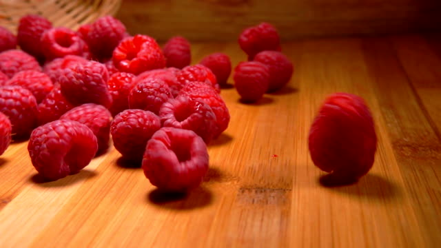 Large juicy raspberries falling from the wicker basket to the wooden table - video