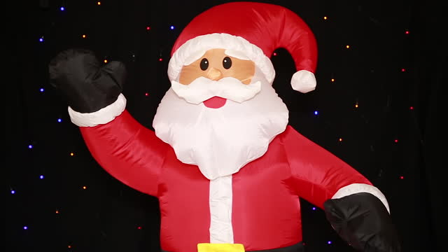 A large life-size inflatable Santa Claus doll in a red suit, swaying merrily, waves a greeting.
