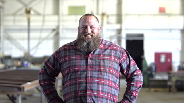 Large man with beard in warehouse walks toward camera