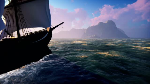 ett stort medeltida skepp till sjöss vid sol uppgången. ett gammalt medeltida skepp seglar till en öde klippig ö. - segelfartyg bildbanksvideor och videomaterial från bakom kulisserna