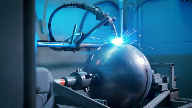 Large metal ball mounted on an automated machine for electro welding work on the production of parts. Replacement of people by the working machines video