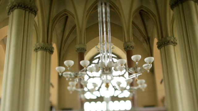 Large modern chandelier in the nave of old gothic church video