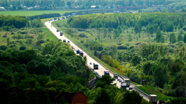 A large number of trucks and cars driving on a long road among the woods and fields. Timelapse Highway m-7 going from Kazan car transporter stock videos & royalty-free footage