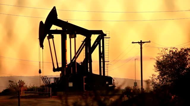 vídeos de stock, filmes e b-roll de óleo de grande derricks no pôr-do-sol cor-de-rosa - rússia