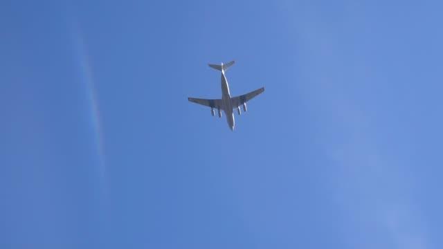 vídeos de stock e filmes b-roll de large plane in the blue sky over moscow slow motion video - maio