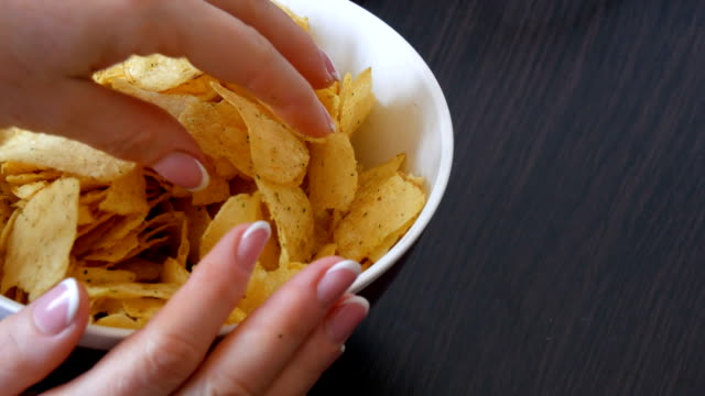 large plate with potato chips on the table. female hands with beautiful manicure take chips - chip komputerowy filmów i materiałów b-roll