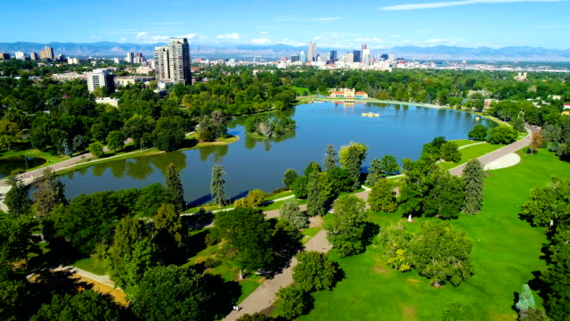 Large Pond reflecting the Denver Colorado Skyline cityscape and surrounding trees at City Park aerial drone view