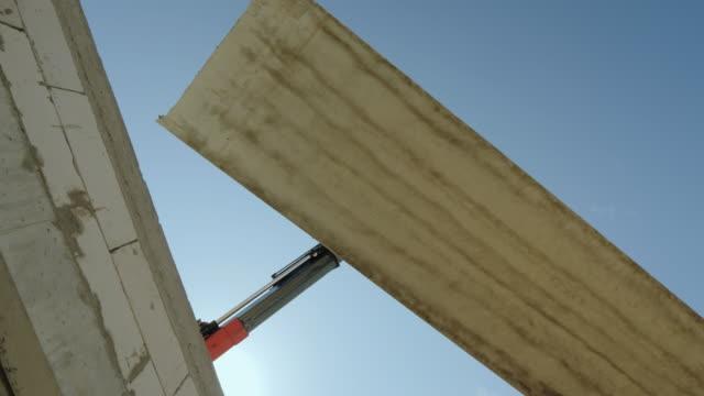 en stor armerad betongplatta hänger på boomen av kranen. farligt yrke begrepp - construction workwear floor bildbanksvideor och videomaterial från bakom kulisserna