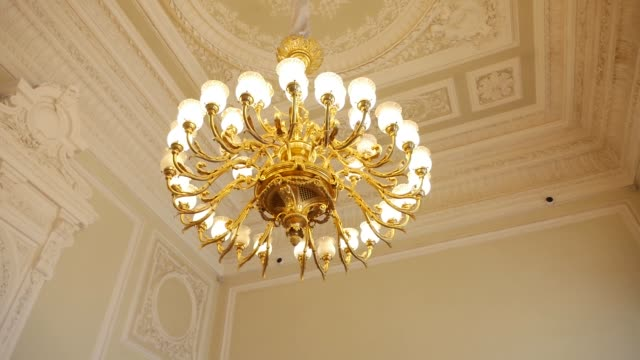 large round gold antique chandelier hanging on the ceiling