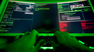 istock Large screen of code for hacker, hands typing malicious code. 1204802238
