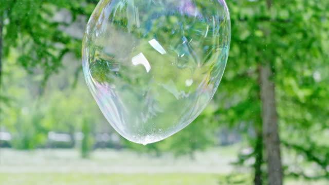 stockvideo's en b-roll-footage met grote zeepbel vliegen en barsten - reus fictief figuur