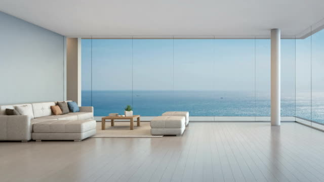 large sofa on wooden floor near glass window with ocean and blue sky background at penthouse apartment, lounge in sea view living room of modern luxury beach house or hotel - guardare il paesaggio video stock e b–roll