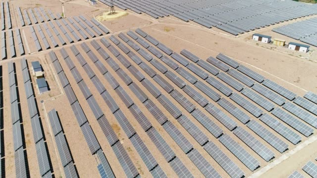 Large solar panels farm in aerial view with a drone. There is the reflection of the sun in the the panels which produce renewable energy, solar energy -  environment and renewable energy concept