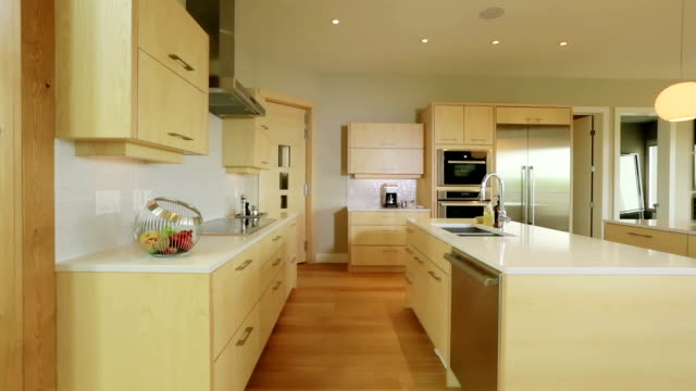 Large spaciuos contemporary home kitchen Roomy large contemporary kitchen with wood cabinets and stainless steel fridge and dishwasher. cabinet stock videos & royalty-free footage