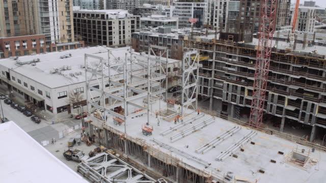 vídeos de stock e filmes b-roll de large steel structure being set in place with a crane - liga desportiva