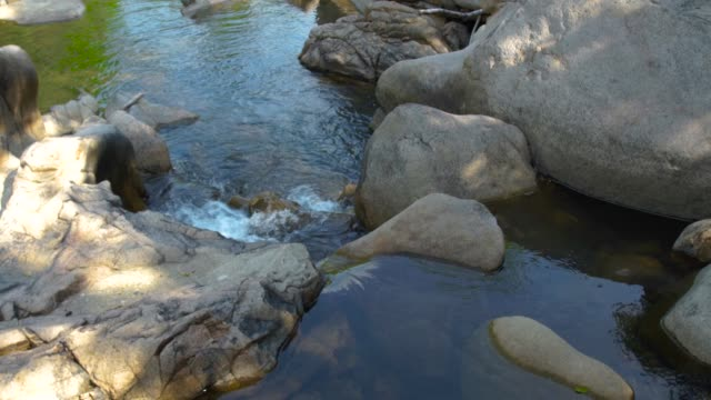 Large stones and rocks in mountain river. Mountain waterfall and stony river in tropical forest. Rapid river flow between big stone creating waterfall