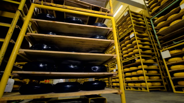 A large storage with racks full of cheese wheels covered in black and yellow wax. 4K. video