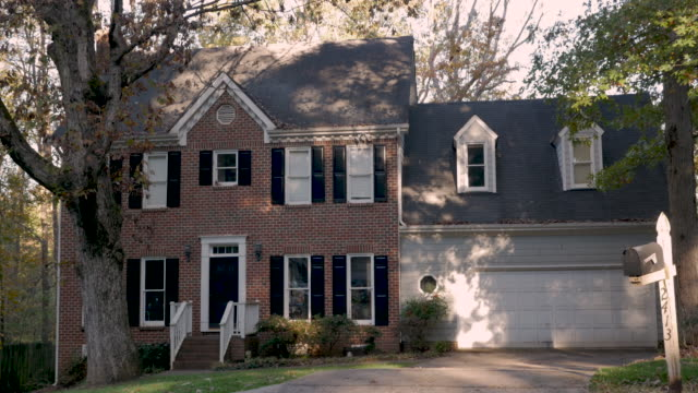 Large suburban home built in the late 1980s with a large tree in the front yard Large two story brick suburban home built in the late 1980s with a large oak tree in the front yard with fall leaves in the autumn mansion stock videos & royalty-free footage