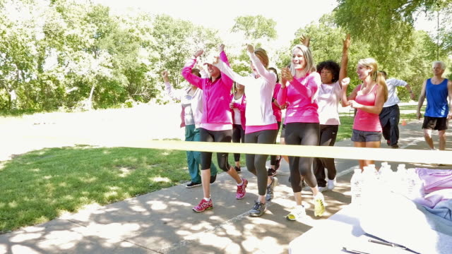 Large team of women crossing finish line during breast cancer awareness race for charity video