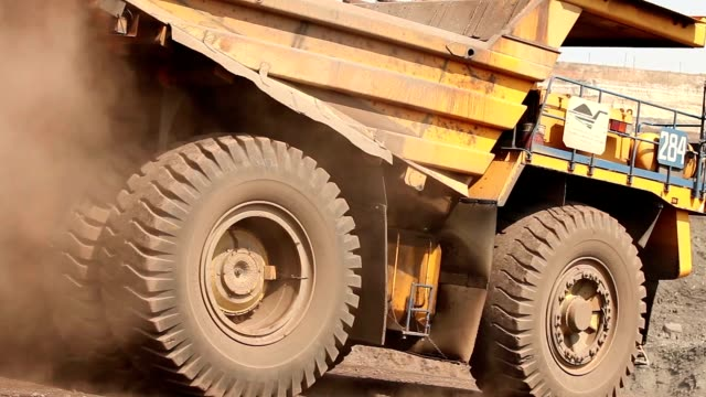 a large tipper digs through a career, an industrial truck dredges cargo in its quarry, a large yellow dumper - ghiaia video stock e b–roll