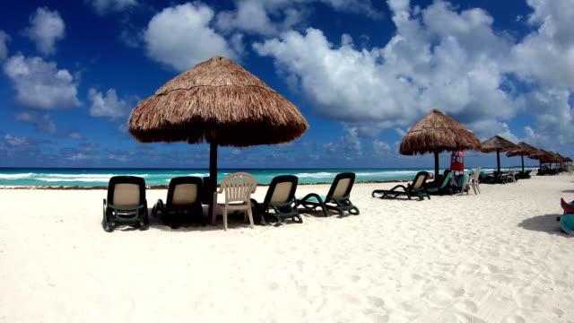stockvideo's en b-roll-footage met groot tropisch strand met palapas - caraïbische zee
