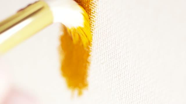 vidéos et rushes de grand pinceau blanc faisant des mouvements lisses et dessinant la ligne par la peinture orange d'huile sur la toile blanche. action. concepts d'arts et de peinture - toile à peindre