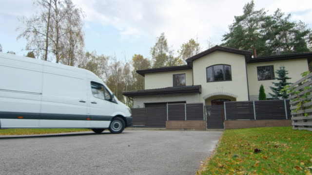 large white van drives to beautiful suburban house. man comes out of the van. outside is clearly visible autumn season. - arrivo video stock e b–roll