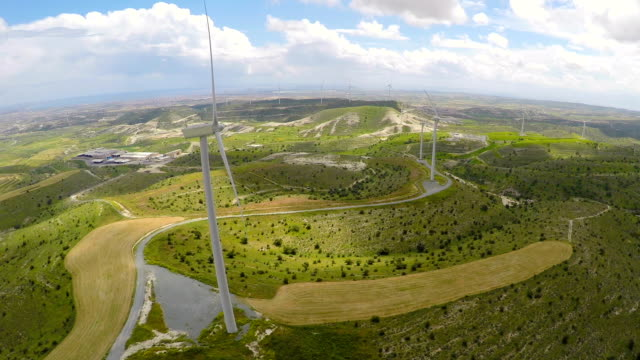 Large wind farm generating electrical power for modern plant, green landscape video