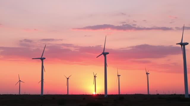 ブレード付きの大型風力タービンは、フィールドのウィンドパークで明るいオレンジ色の夕日の青空に対してタイムラプス。風車のシルエット、大きなオレンジ色のサンディスク夏のレンズ� - オルタナティブカルチャー点の映像素材/bロール
