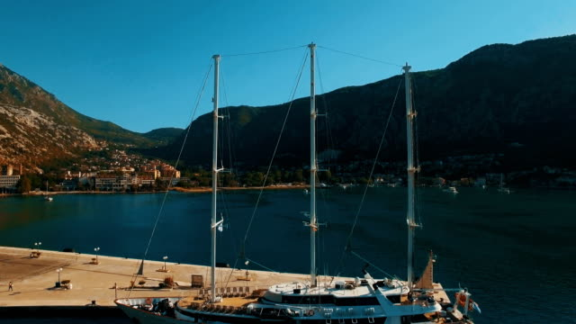 A large yacht stands at the pier in the bay Kotor, Montenegro. Aerial footage A large yacht stands at the pier in the bay Kotor, Montenegro. Aerial drone footage 4K UHD pedal pushers stock videos & royalty-free footage